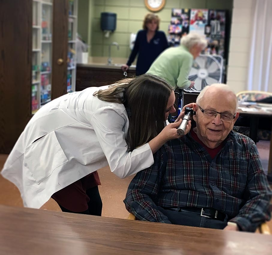 Dr. Brooke Lewandowski checks an ear on Luther Manor resident Ron Wells during a recent outreach visit.