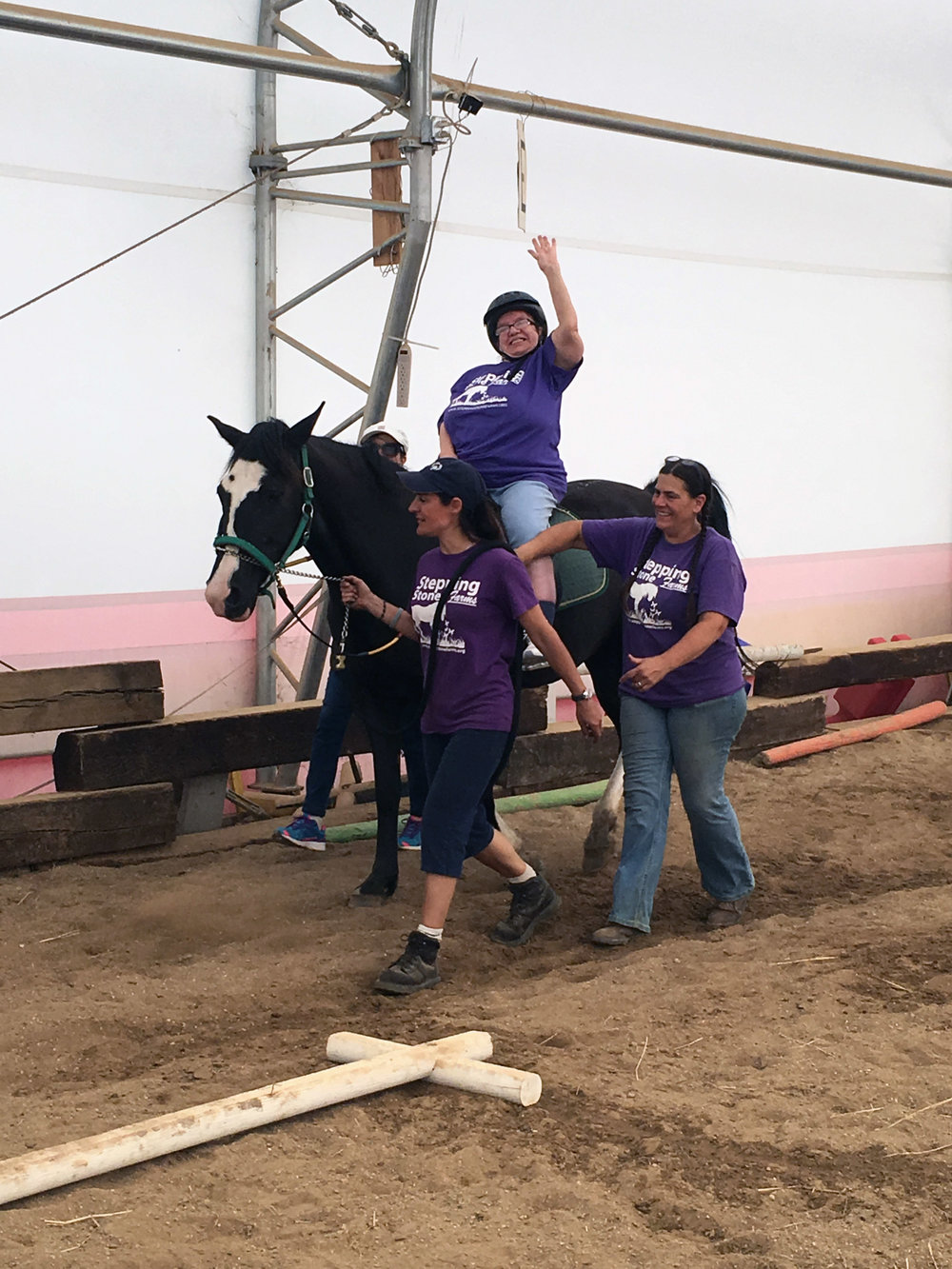 Pamela waves as Yvette and Lia walk her safely around the indoor arena at Stepping Stone Farms.
