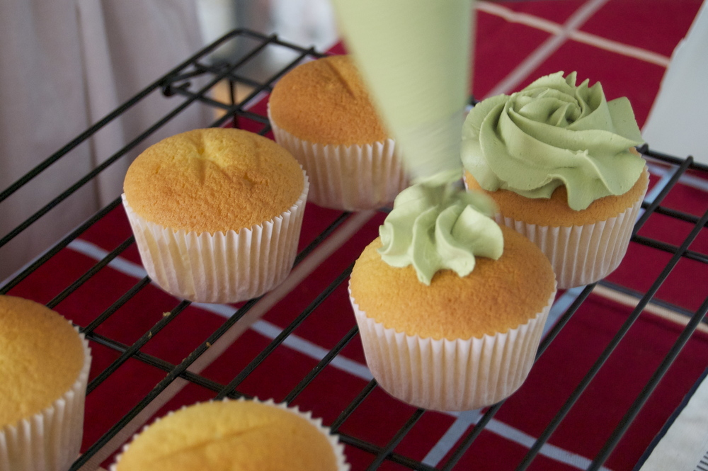 Piping green tea frosting onto the cupcakes.