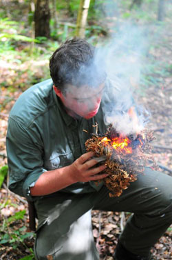 Paul Kirtley breathing life into a tinder bundle. (Photo courtesy of www.FrontierBushcraft.com)