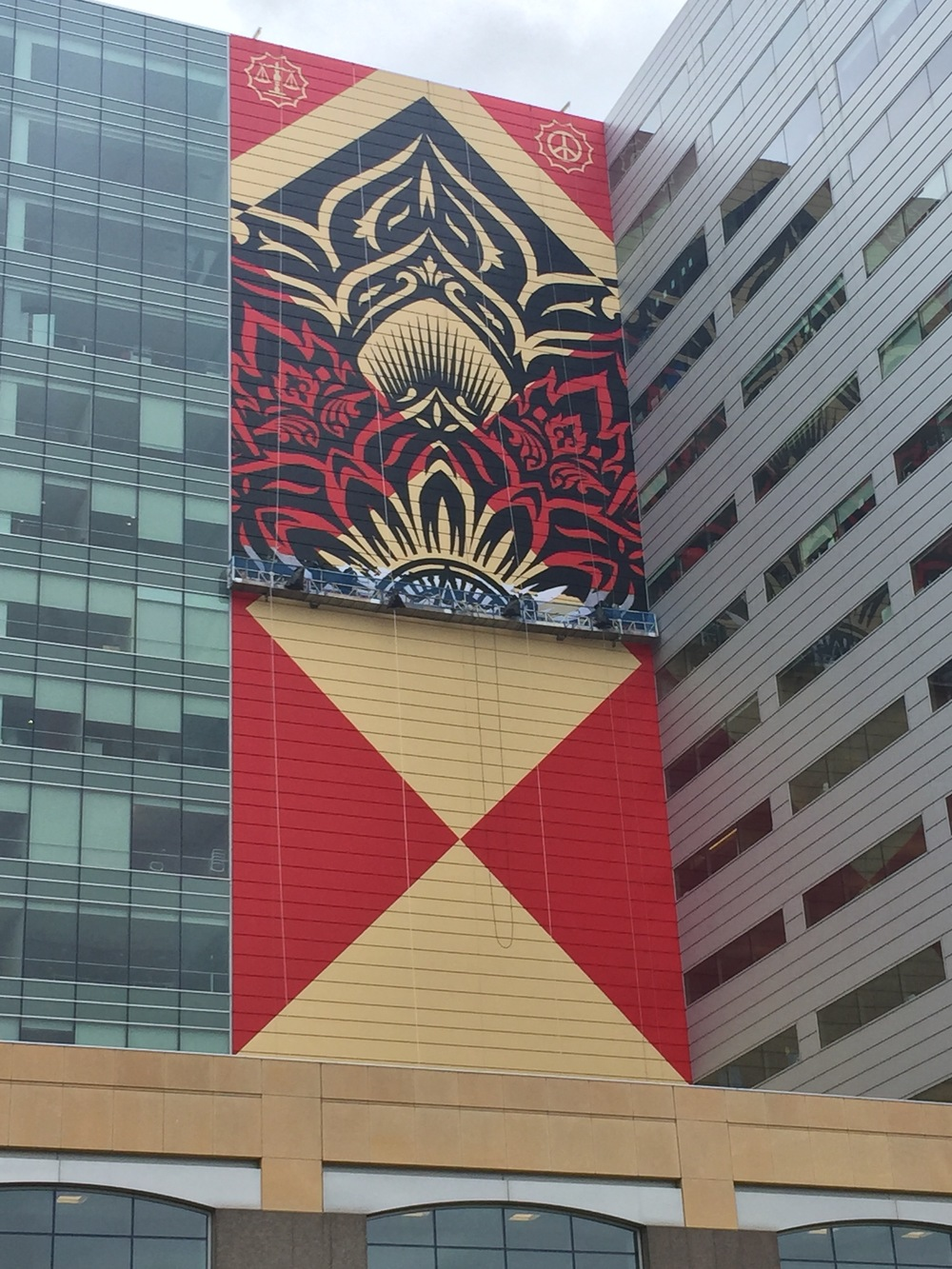 Shepherd Fairey  works on a new mural on the side of One Campus Martius.