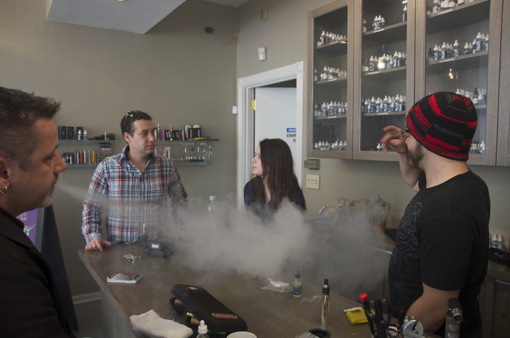 Jared Yucht, (left-center) owner of Smoque Vapours, with employees Stephanie Bowman and Michael Haynes. Frequent customer Scott Norris (far left) takes a drag from a modified vaporizer.
