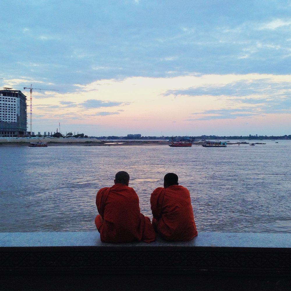 Two monks enjoy the sunset along the Mekong River in Phnom Penh, Cambodia