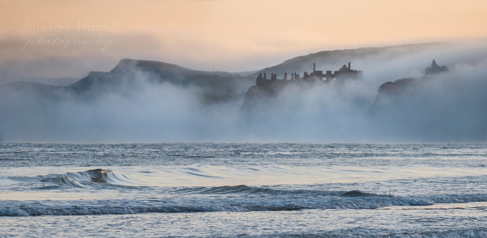 Dunluce Castle finally and briefly emerges from the early morning fog.