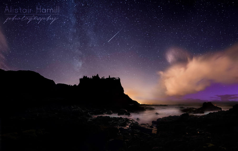 A meteor fireball streaks across the sky above Dunluce Castle.