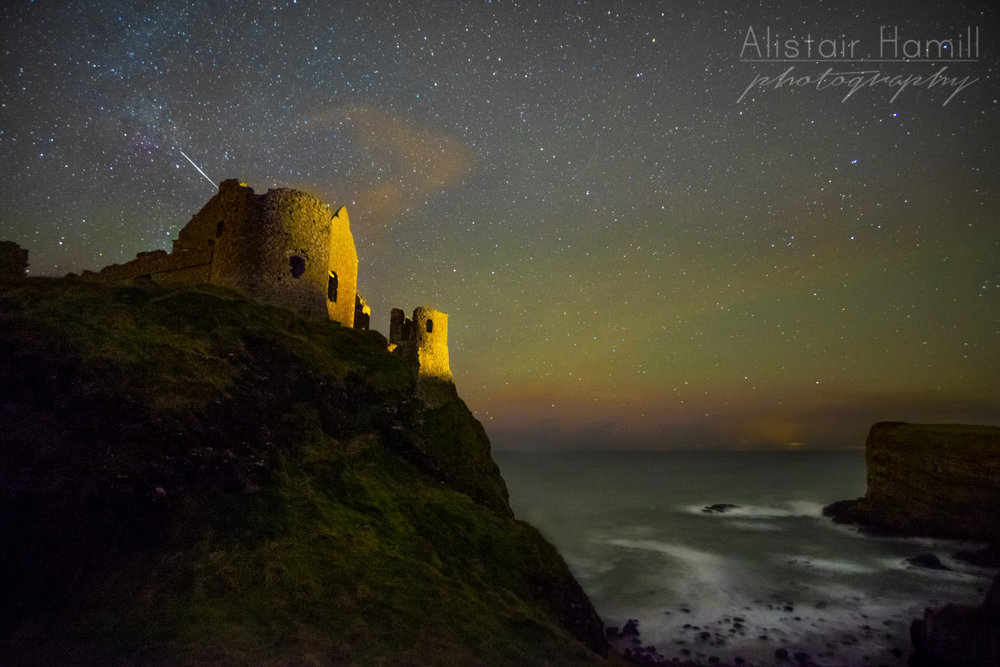Airglow appearing behind Dunluce Castle. The light streak behind the castle is an iridium flare, the sun glinting off a passing satellite.