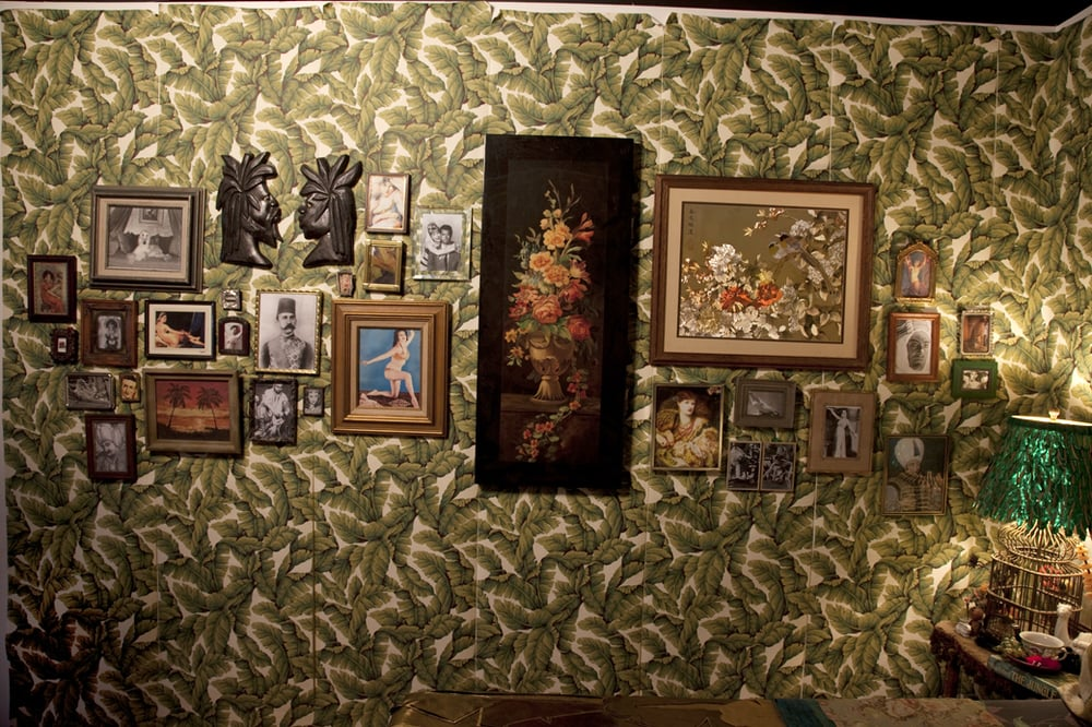 So Exotic  10' x 27'  Installation  2008-2010  Image credit Lisa Talbot  Wall hung salon style of images found and framed with the whites of all eyes gold leafed.