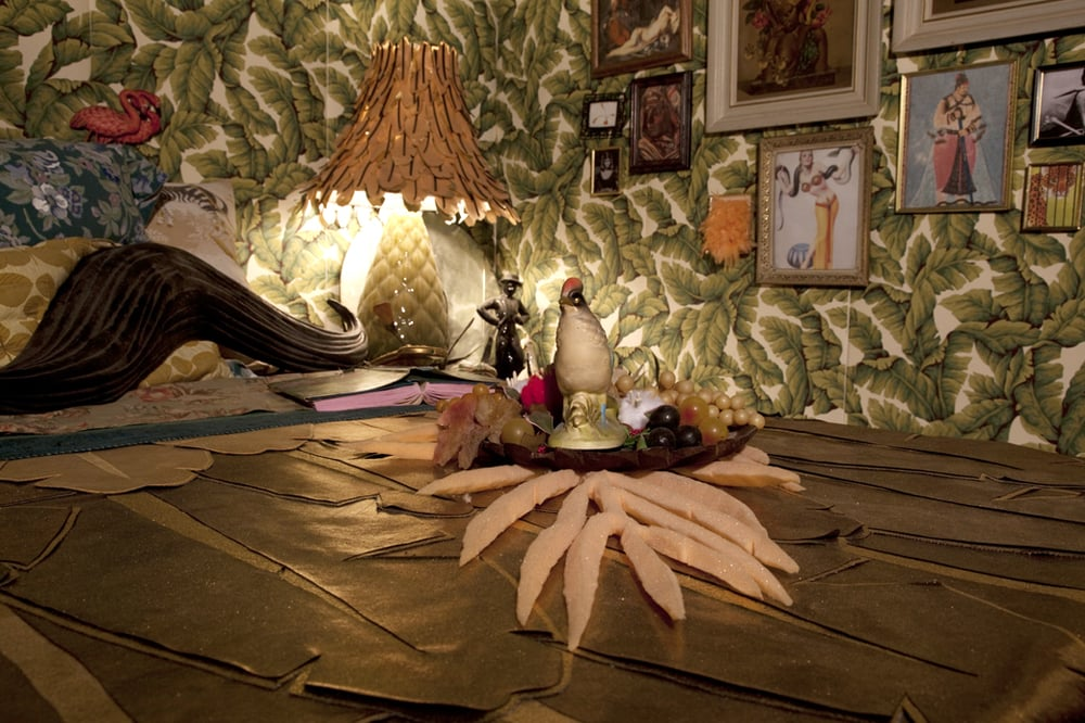 So Exotic  10' x 27'  The foam palm from 'So Exotic in Three Parts' with a carved wooden fig leaf tray on top, filled with plastic fruit and the tchotchke that inspired the large pheasant sculpture at the entrance.  2008-2010  Image credit Lisa Talbot
