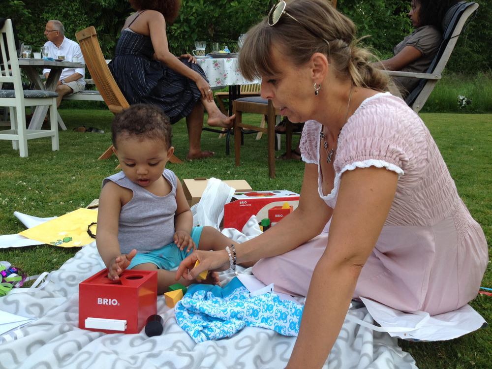 Helena sitter och leker med ett av barnen.