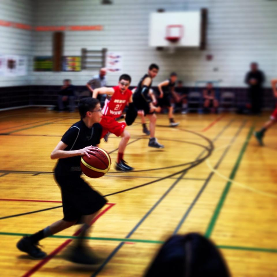 Parker taking it down court during a basketball tournament.
