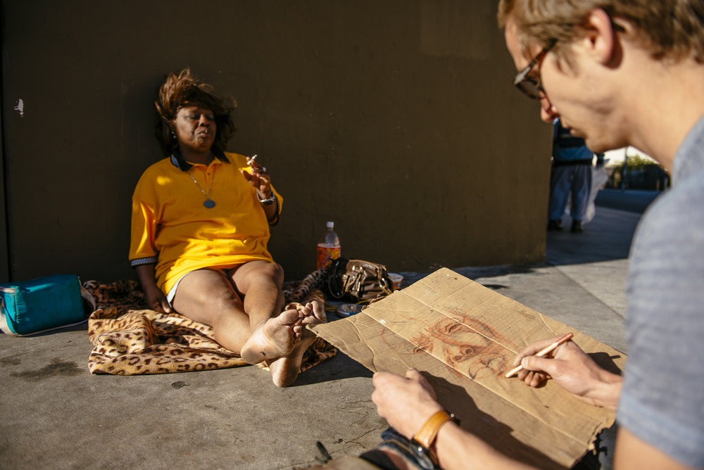 Senior Jason Leith draws a portrait of Roberta, a woman he met while walking the streets of Skid Row. For the last few months, Leith has spent time getting to know men and women who are living on Skid Row, drawing their portraits on reclaimed materials and hearing stories about their lives.
