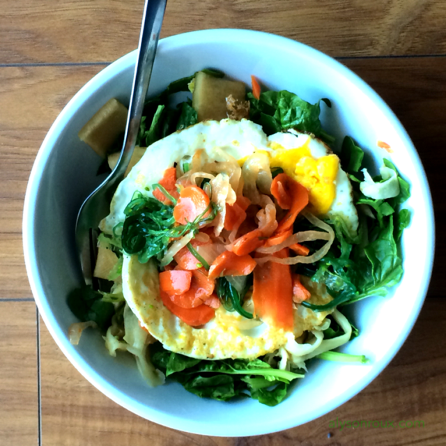 This bowl includes raw spinach, fermented carrots and daikon, raw sweet seaweed salad, and a pastured fried egg.