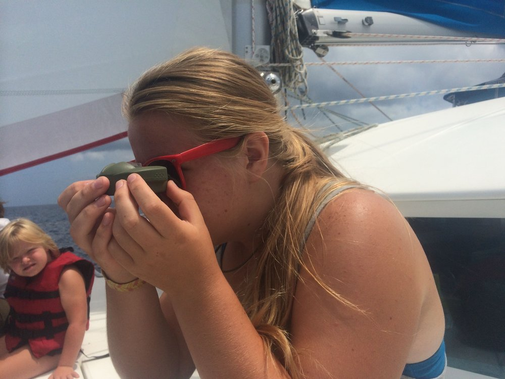 Karina taking a bearing with a handheld compass.