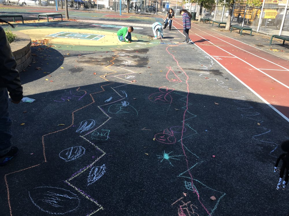 Groups of students worked together to create giant racetracks, mazes, and hopscotches and test them out.