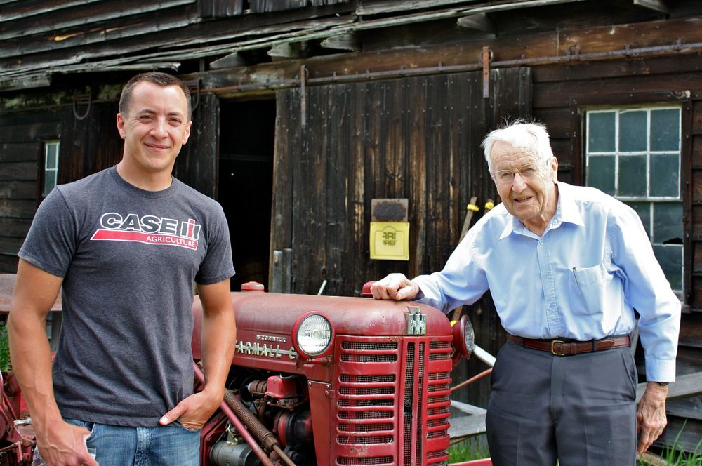 Ev and his grandson Tim in front of their antique Farmall tractor