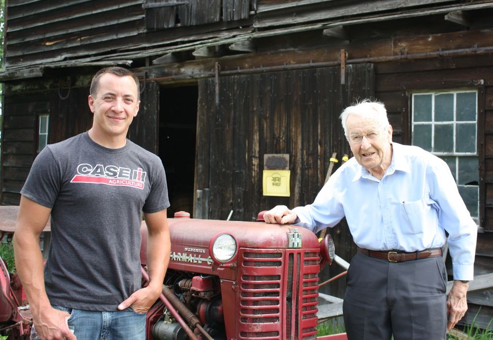 Tim Rau with his grandfather, Everett, in in front of one of their historic Dutch barns.