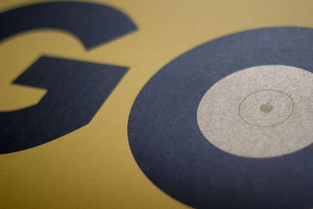 Old and new techniques collide in The Counter Press's interpretation of The Maccabees' atmospheric track, resulting in a deceptively simple letterpress design with depth in the detail. Using the physical record to form the 'O' in the track name, they set about finding a complementary typeface for the 'G', settling on the geometric curves of FF Super Grotesk®, laser cut to match in size perfectly.   Technique:  Letterpress  Type:  FF Super Grotesk®,  FontFont ; Monotype Caslon