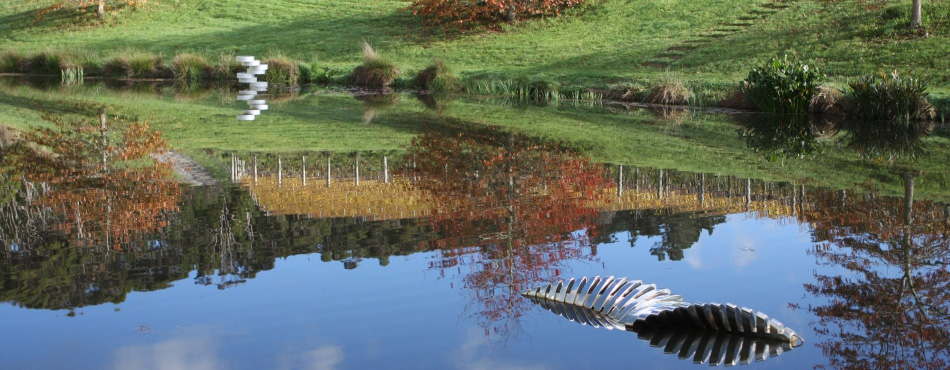 Sculptures peeking out of the water with the autumn vines reflected in the lake's still surface.
