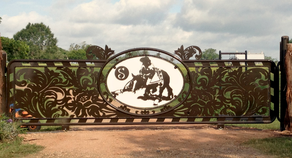 EL SUENO  The inspiration for this art is the old hand tooled wallets that came in kits. I never made one but I love the classic western scrollwork.The owner wanted his two favorite horses on the gate, so the other side has a  different horse. We also have LEDS behind the horses so they glow at night. 4' x 16'  Slider-Custom