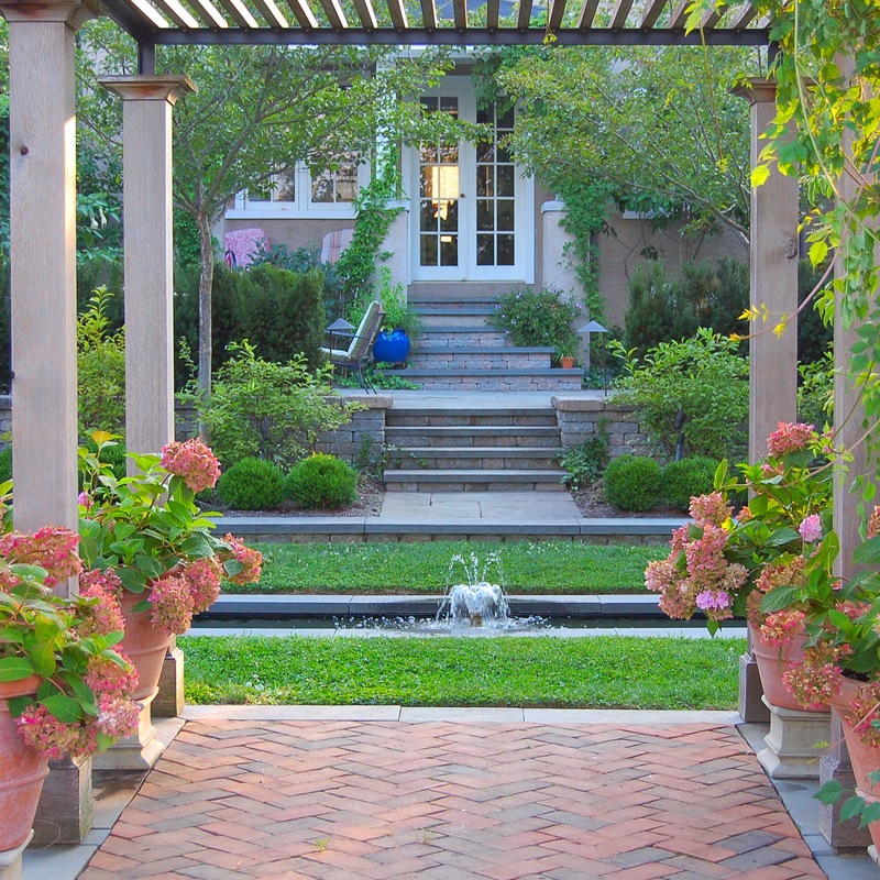 French influenced garden in Lancaster Pa. A pergola with brick and flagstone patios and lush planting. A central water feature with a firepit and outdoor lighting.