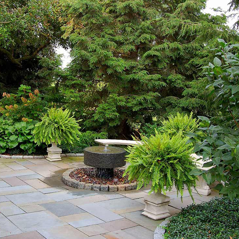 Traditional garden Lancaster Pa. by Fernhill Landscapes. Millstone fountain, flagstone patio, stone walls, lush planting, cedar deck.