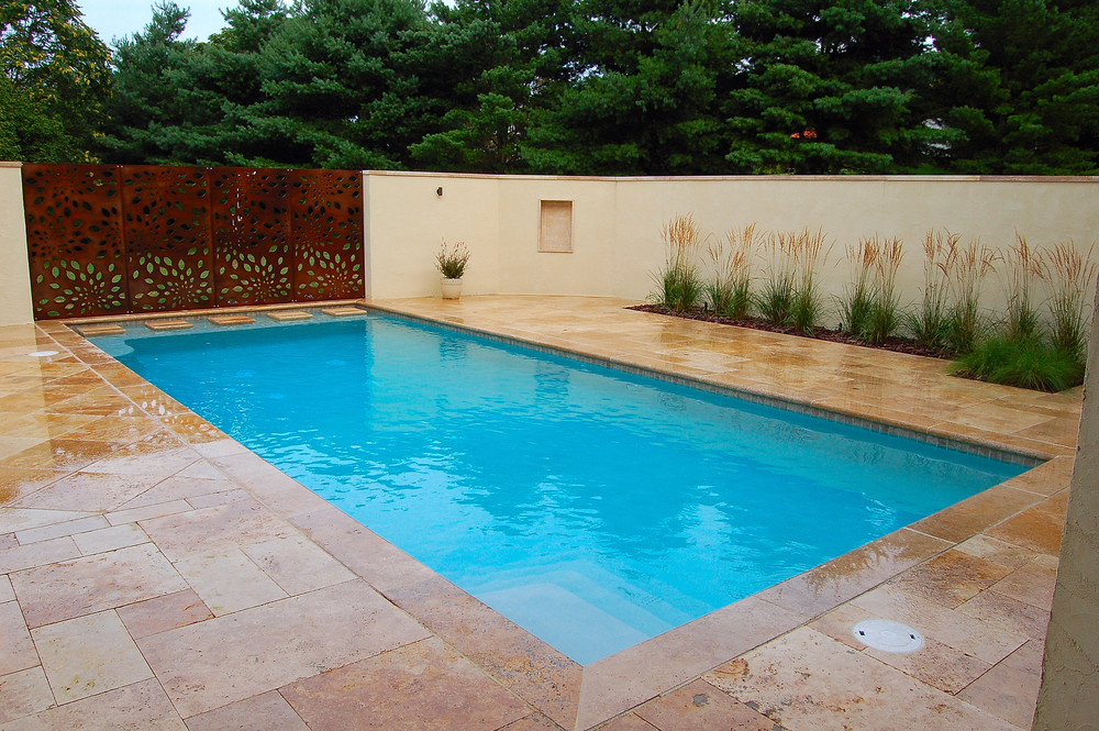 Lancaster landscaping by Fernhill Landscapes, Travertine patio, outdoor fireplace and swimming pool with outdoor lighting.
