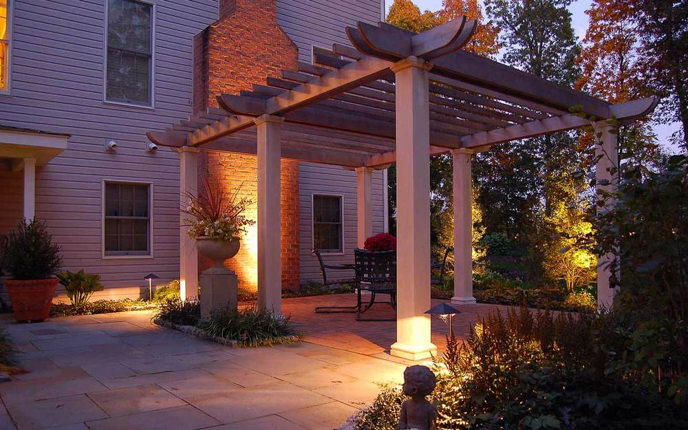 The landscape design contains a wood two tone pergola