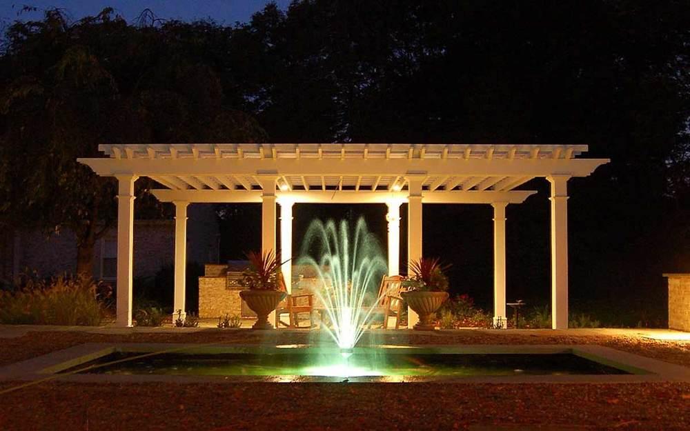 Fountain, urns and pergola at night