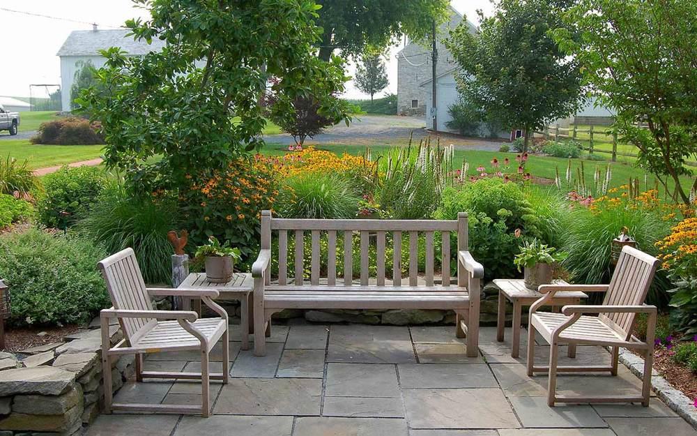 Outdoor teak furniture on fieldstone patio