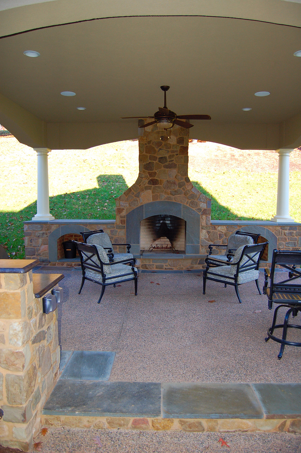Covered outdoor fireplace and ceiling fan