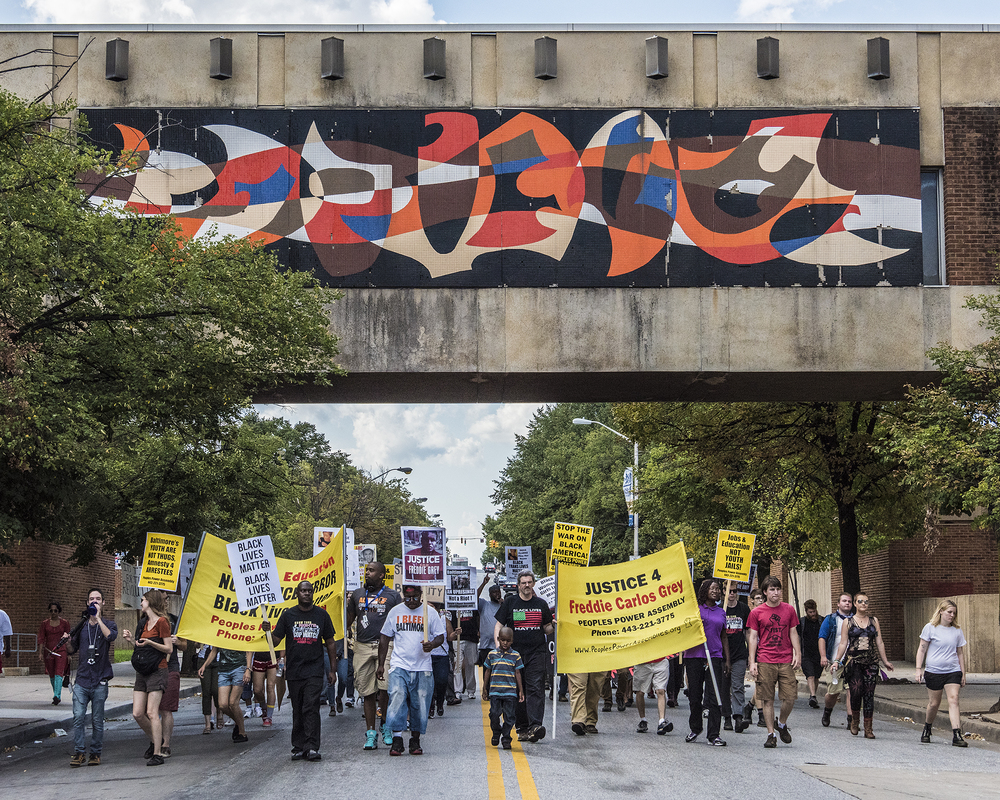 Protesters march under the Furman L. Templeton Preparatory Academy pedestrian overpass on Pennsylvania Avenue in Baltimore.