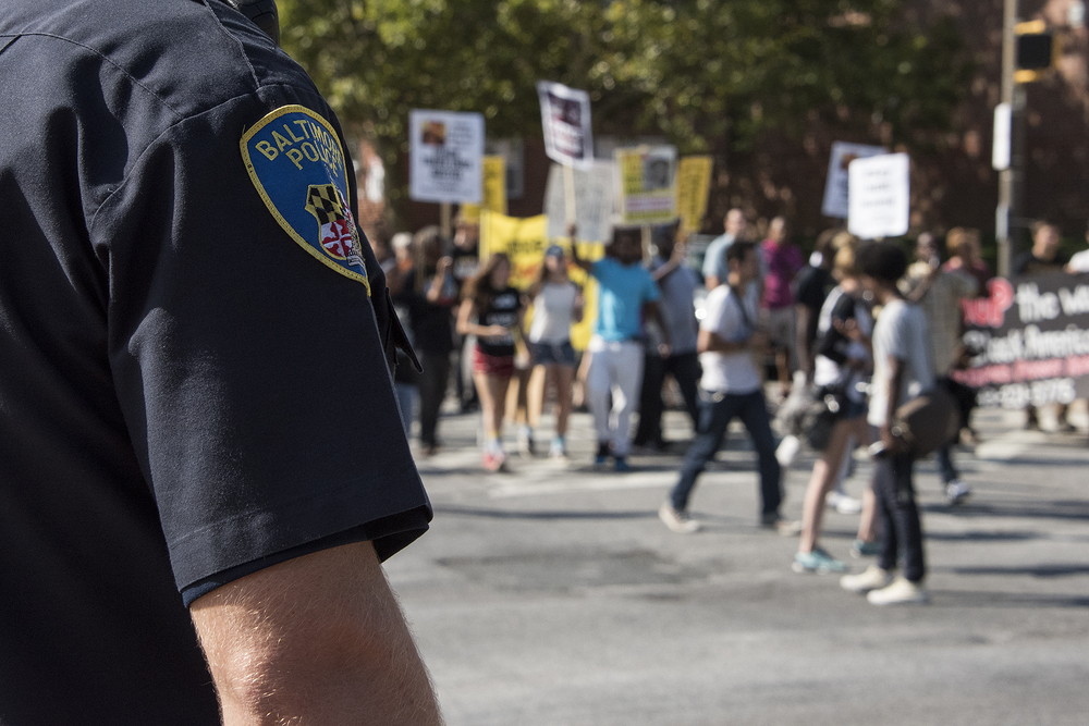 Baltimore City Police Officers stand ready as the protestors march through Baltimore.