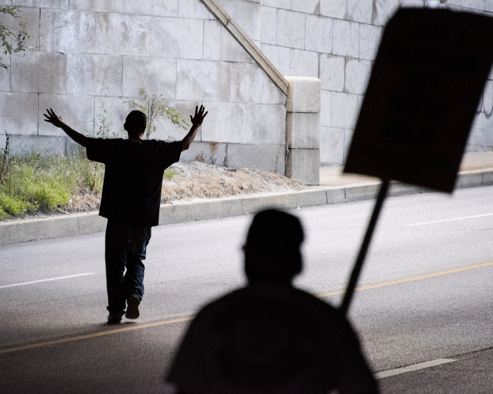 A protester holds his hands in the air as he leads the march down North Howard Street under the West Mount Royal Avenue overpass.