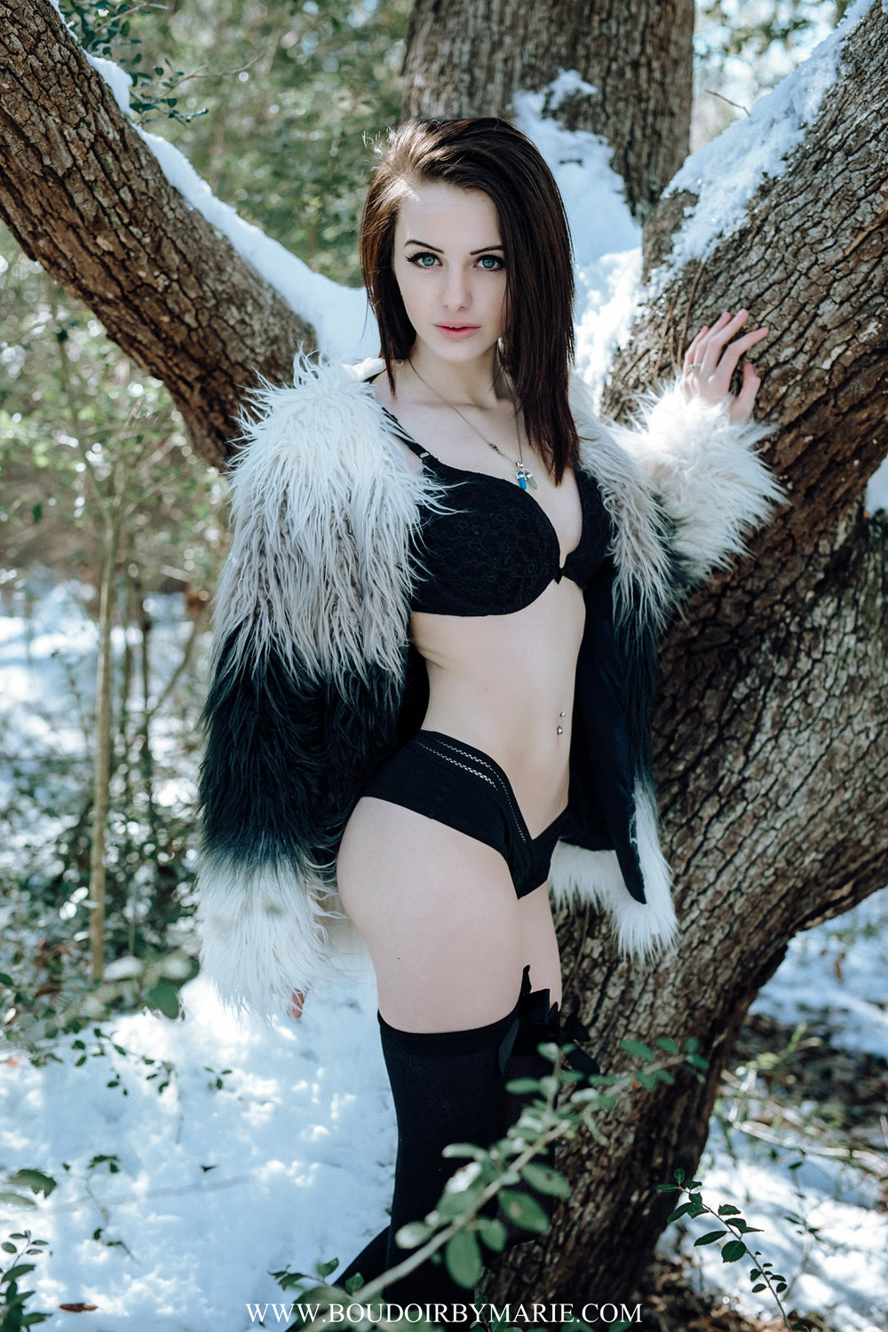 Outdoor snow boudoir photo of girl in black bra and panty set.