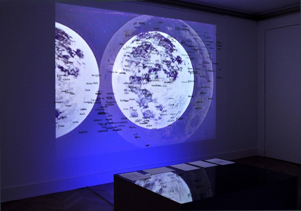 La Nuit de Chateaubriand II , 2017  wooden pedestal, fluorescent tubes, filters, partition of words, video, sound, loop 18min (organ Adam Bernadac)   on the pedestal: printed texts, documents dimensions variable  installation view,  Nuits Américaines , Maison de Chateaubriand, Châtenay-Malabry, 2017-2018