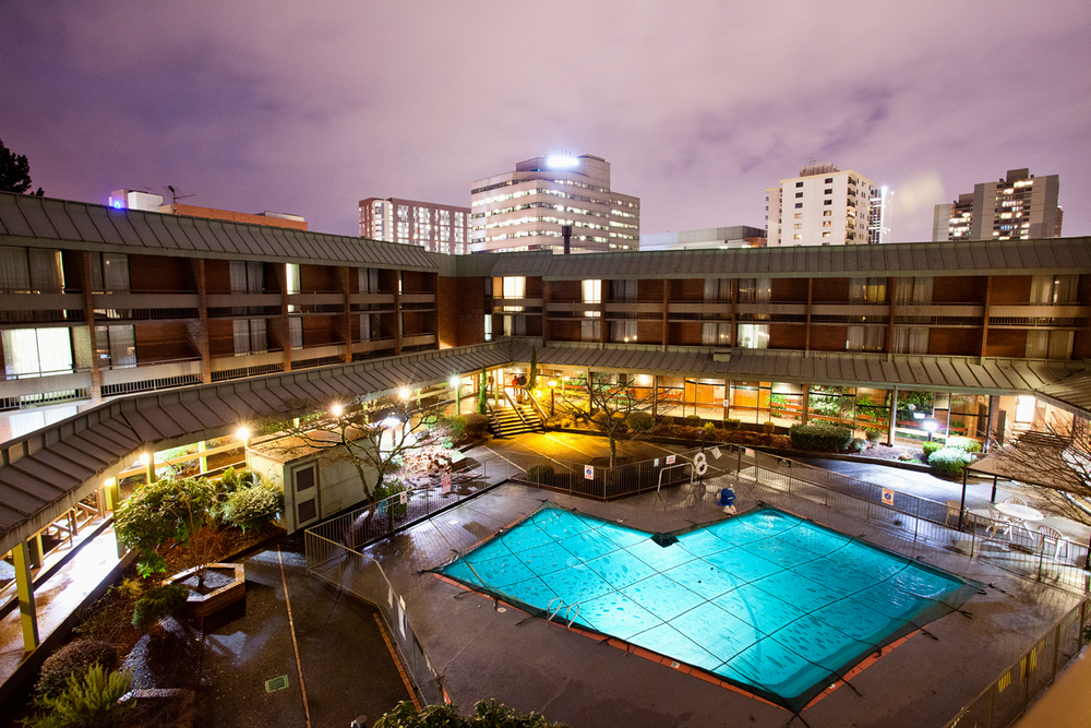 A hotel courtyard and swimming pool under a purple night sky, with the Portland, Oregon skyline visible in the background.