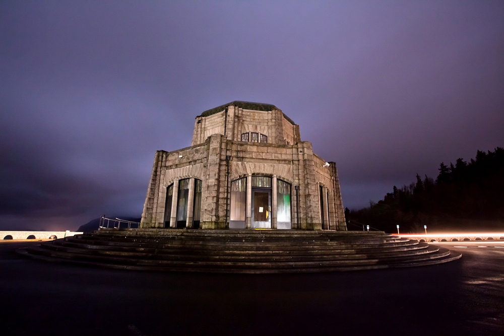 The Vista House at Columbia River Gorge illuminated on a cloudy night with car trails.