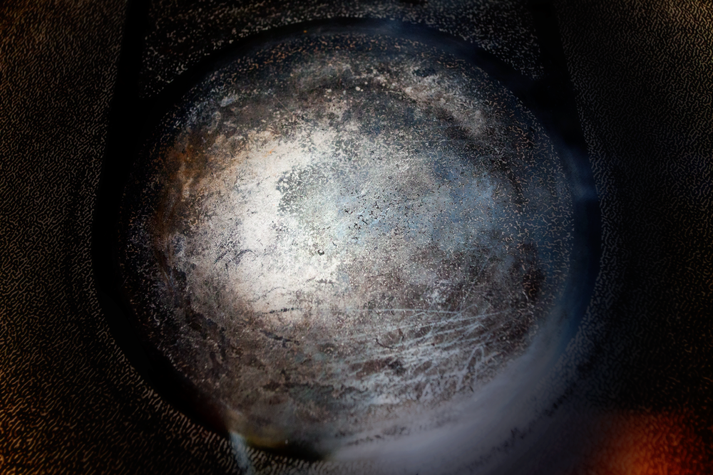 A gritty electric stove top that resembles a textured grey planet in space.