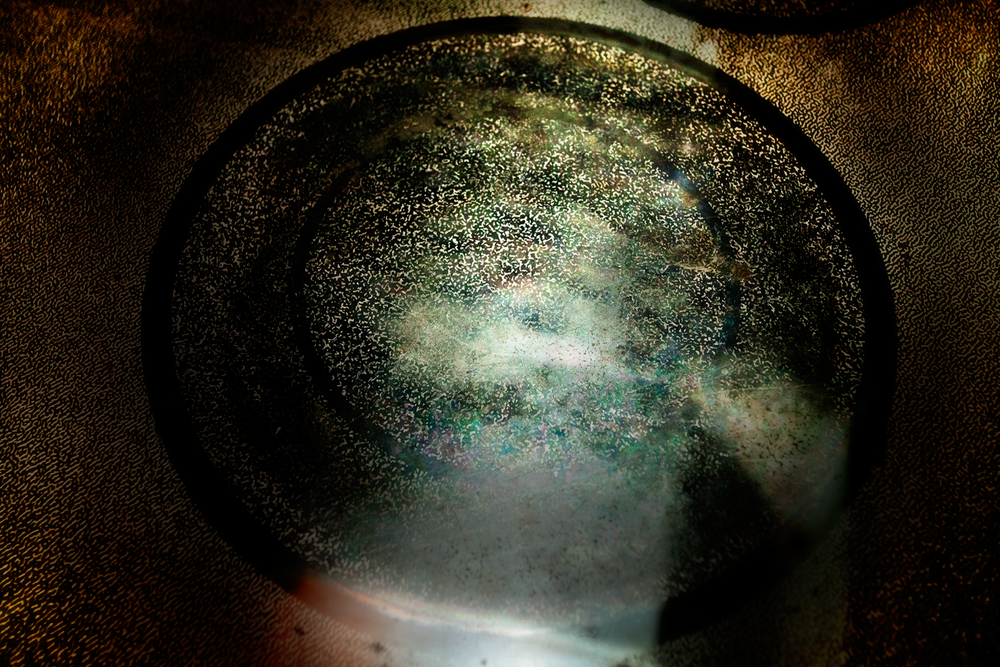 A gritty electric stove top that resembles a green nebula surrounded by stars in space.