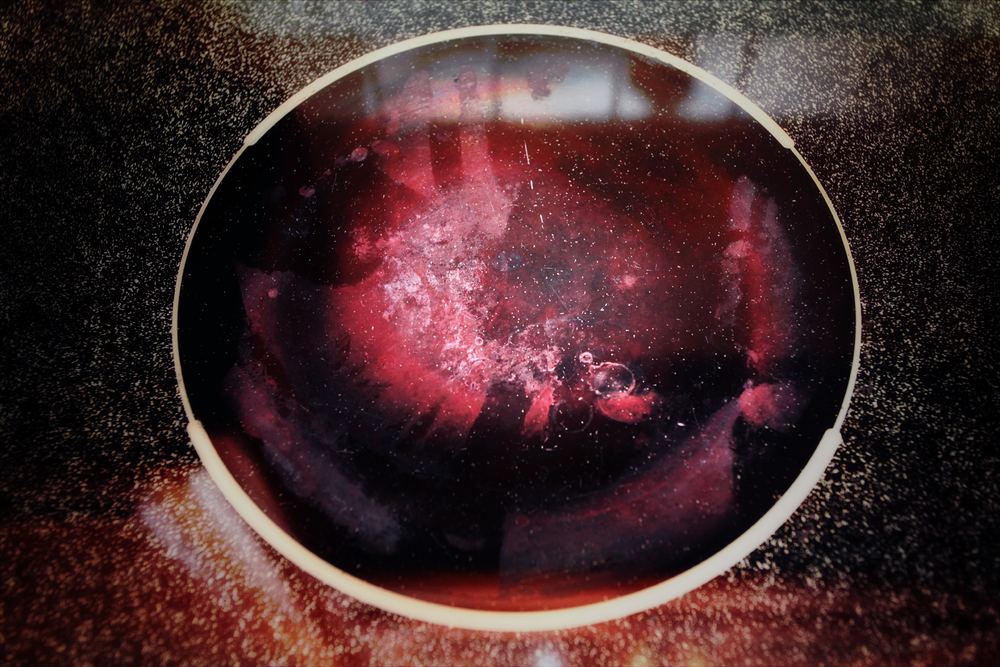 A gritty electric stove top that resembles a pink nebula surrounded by stars in space.