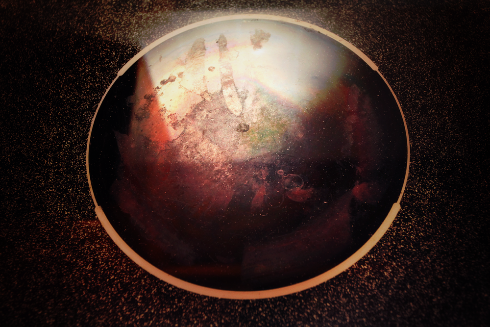 A gritty electric stove top that resembles a red planet with auroral activity in space.