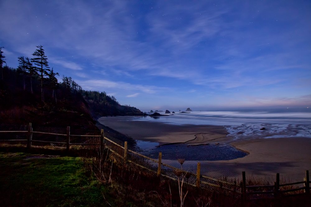 A nighttime landscape of Indian Beach, Oregon depicting a starlit sky and serene ocean tide.