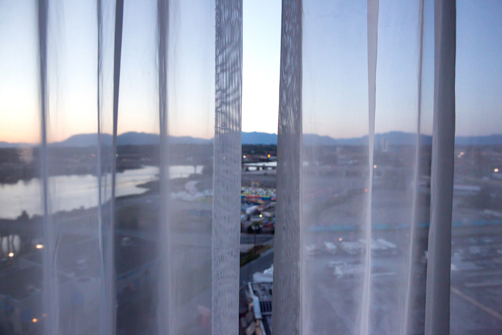 A partially open window curtain revealing the city of Vancouver, Canada below.