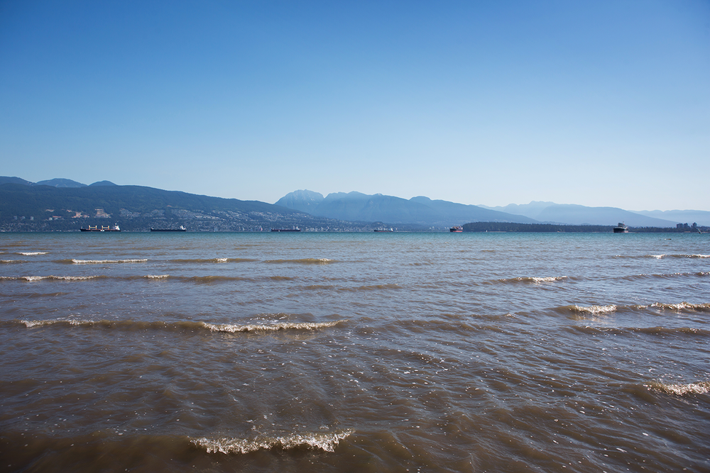 English Bay seen during low tide from Spanish Banks Beach on a cloudless day in Vancouver.
