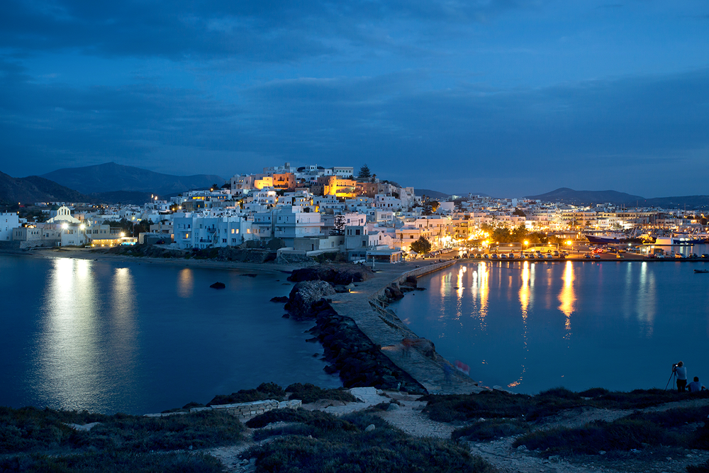 The whitewashed Greek village of Chora seen at night from the Portara.