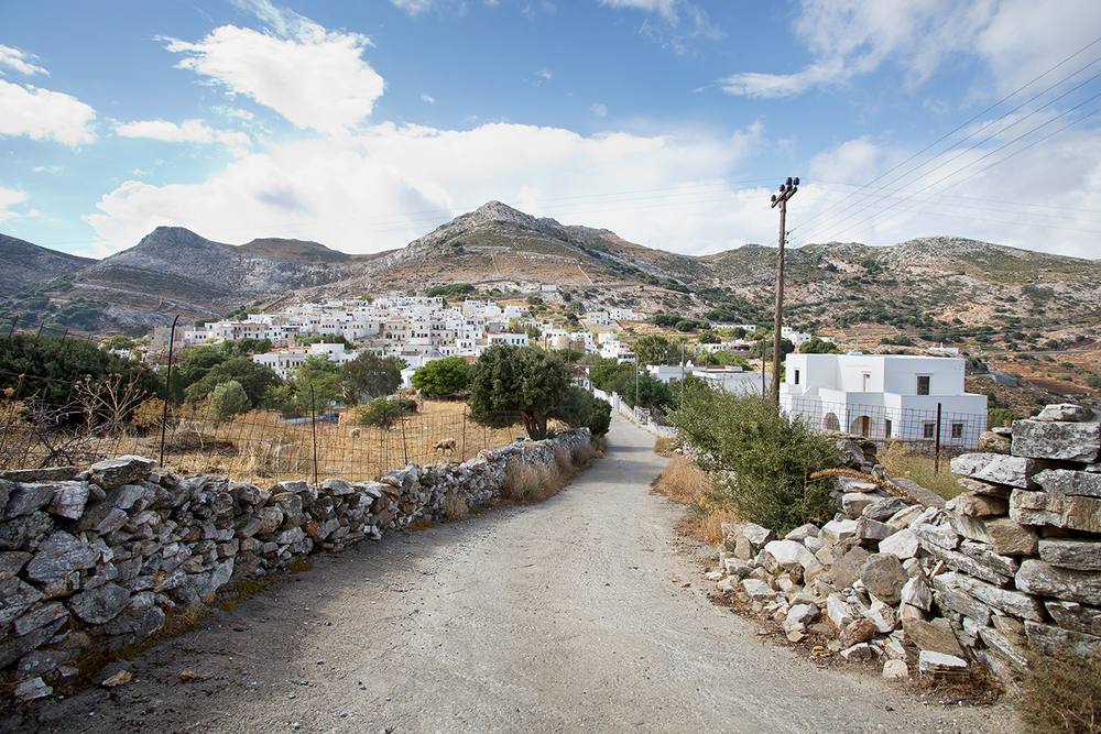 A dirt road and stone fence leading to the mountainous village of Apeiranthos in Naxos, Greece.