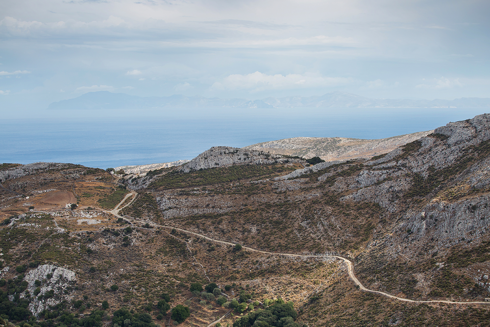 A winding road running through the mountainous coast of Naxos, Greece, with the Aegean Sea in the background.
