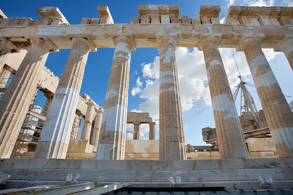 A close up of the Parthenon and its pillars undergoing renovation beneath a dramatic blue sky.