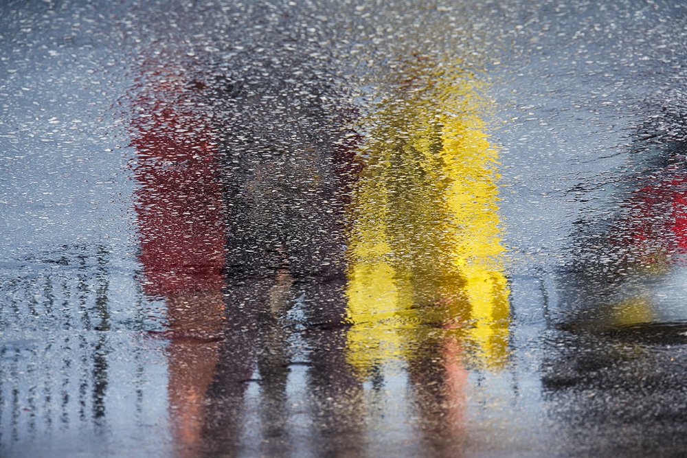 A puddle reflection on asphalt of tourists wearing colorful coats after a rain storm.