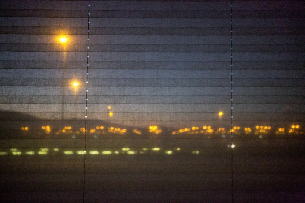 A colorful sunset and highway lights seen through a transparent window shade.